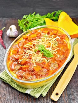 Gachas de maíz con albóndigas, salsa de tomate, ajo y calabaza, espolvoreado con queso, albahaca en una sartén sobre una servilleta sobre fondo de tablero de madera oscura.