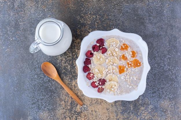 Gachas de muesli con frambuesas y un tarro de leche