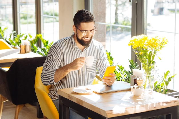 Gadget moderno. buen hombre alegre sentado con su teléfono inteligente mientras toma café en la cafetería