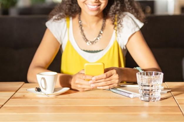 Gadget moderno. enfoque selectivo de un teléfono inteligente amarillo en manos de una mujer joven positiva