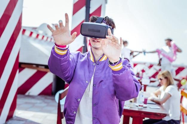 Gadget de realidad virtual. morena complacida manteniendo una sonrisa en su rostro mientras levanta las manos