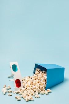 Gafas 3d con palomitas de maíz derramado sobre fondo azul