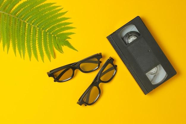 Gafas 3d, videocasete, hoja de helecho sobre un fondo amarillo. vista superior, minimalismo