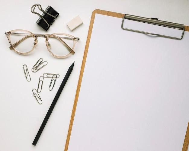 Gafas y artículos de papelería cerca del portapapeles
