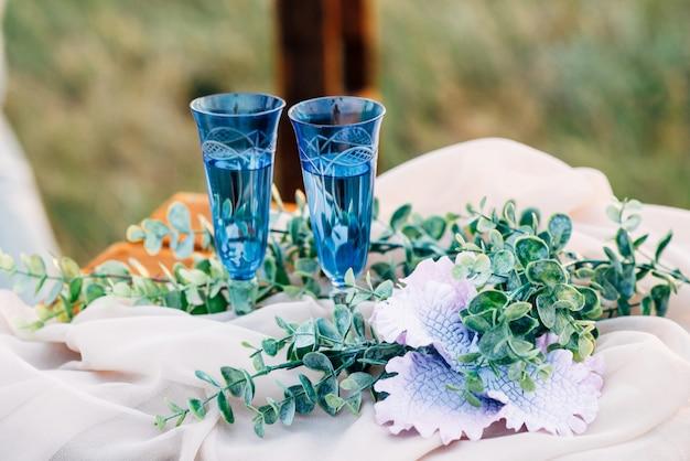 Gafas azules junto a flores sobre la mesa