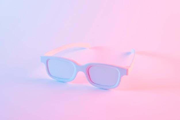 Gafas blancas contra el fondo rosa