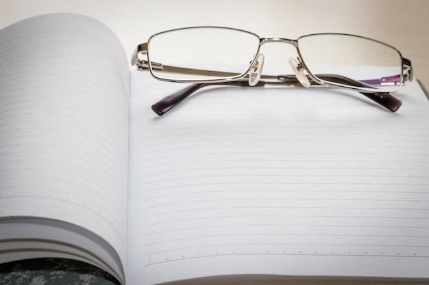 Gafas y bloc de notas con página en blanco