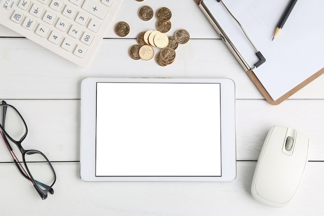 Gafas, calculadora, monedas y tableta en blanco escritorio aseado