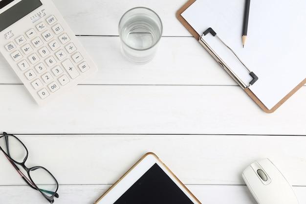 Gafas, calculadora y tableta en blanco escritorio aseado