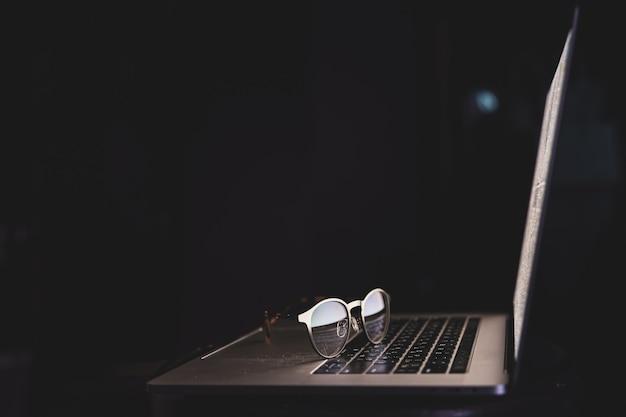 Las gafas cerca de la computadora portátil reflejan la luz de la pantalla en el espacio oscuro de la copia