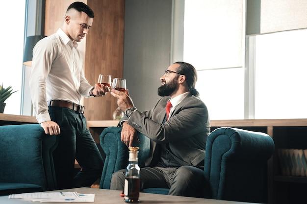Gafas clang. prósperos socios comerciales haciendo sonar sus vasos bebiendo coñac después del trabajo