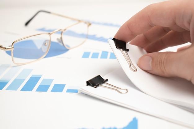 Las gafas se colocaron en los documentos del informe de datos, gráficos y tablas para la elaboración del plan de negocios.
