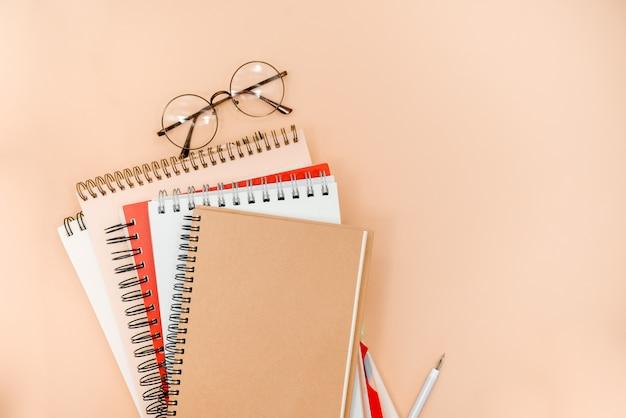 Gafas y cuadernos sobre un fondo abstracto de color beige