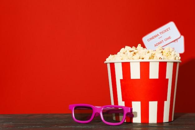 Gafas, cubo rayado con palomitas de maíz y entradas sobre fondo rojo.