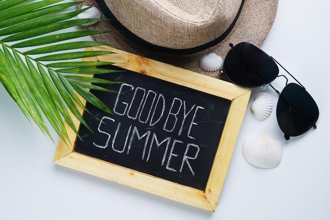 Gafas de sol, sombrero fedora, hoja de palma, conchas marinas y sala de pizarra