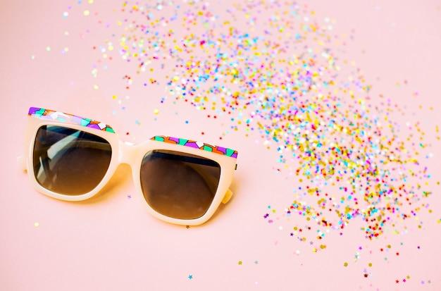 Gafas de sol y confeti aislados en el fondo