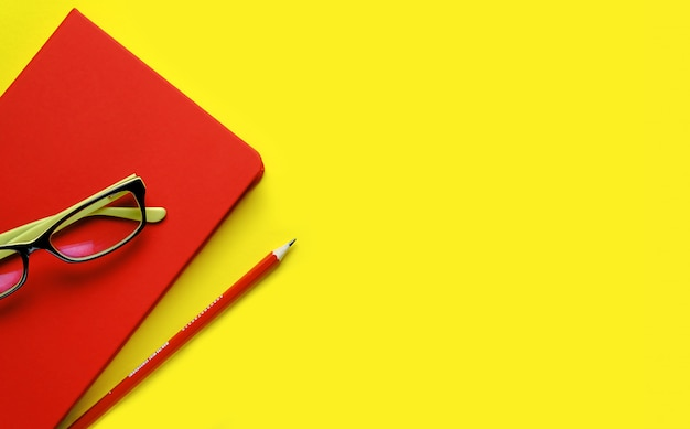 Las gafas están en un cuaderno rojo, junto a un lápiz, sobre un fondo amarillo. lugar de trabajo independiente, empresario, empresario.