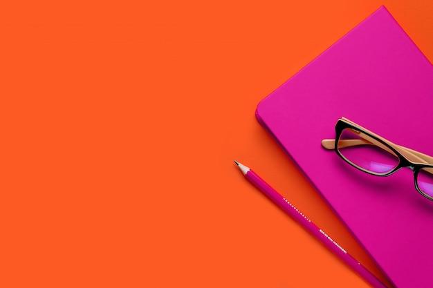 Las gafas están sobre un cuaderno rosa, junto a un lápiz, sobre un fondo de exuberante lava. lugar de trabajo independiente, empresario, empresario. copiar espacio para texto.