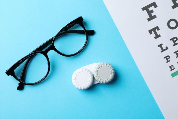 Gafas, estuche para lentes de contacto y tabla optométrica sobre superficie azul, vista superior