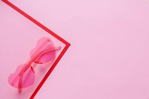 Gafas con forma de corazón rosa sobre un fondo rosa delicado con lugar para texto