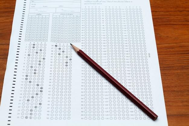 Gafas y lápiz en forma de prueba estandarizada con respuestas burbujeadas y un lápiz, se centran en responder