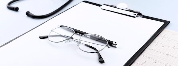 Gafas y lápiz en el portapapeles con estetoscopio y cardiograma sobre fondo azul.
