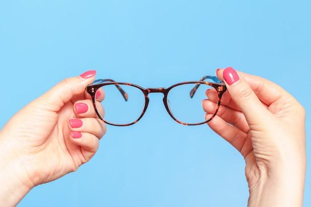 Gafas de lectura modernas. la mujer está tomando gafas ópticas