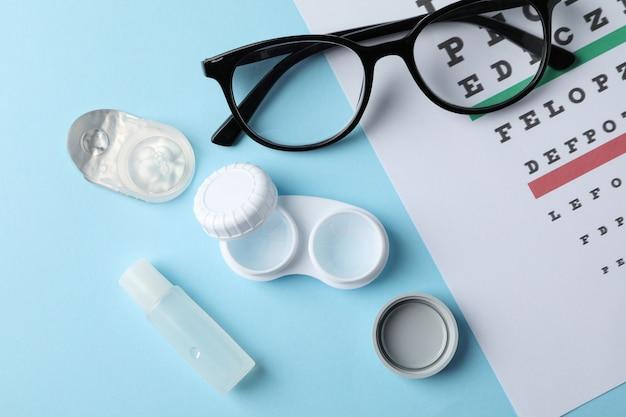 Gafas, lentes de contacto y tabla de examen de la vista sobre superficie azul, vista superior