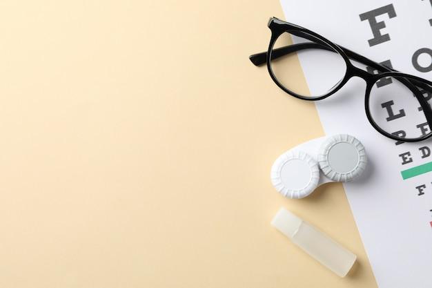 Gafas, lentes de contacto y tabla de prueba ocular sobre fondo beige, vista superior