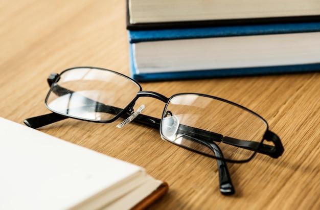 Unas gafas y libros de concepto educativo, académico y literario.