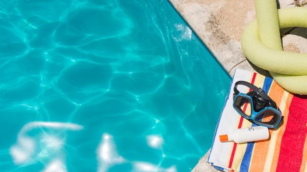 Gafas con loción sobre toalla cerca de juguete y piscina.
