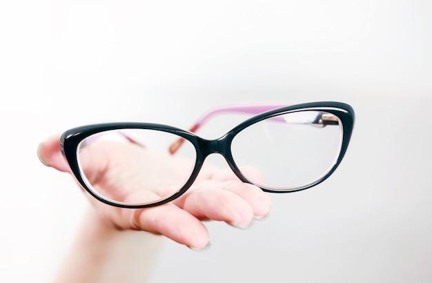 Gafas en la mano femenina, gafas en la mano de una mujer, manos extendidas con gafas, acostarse sobre las palmas de las manos