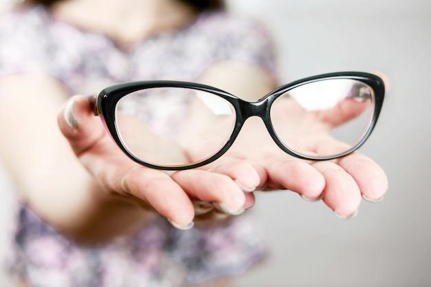 Gafas en mano femenina, gafas en mano de mujer, manos extendidas con gafas, recostarse en las palmas