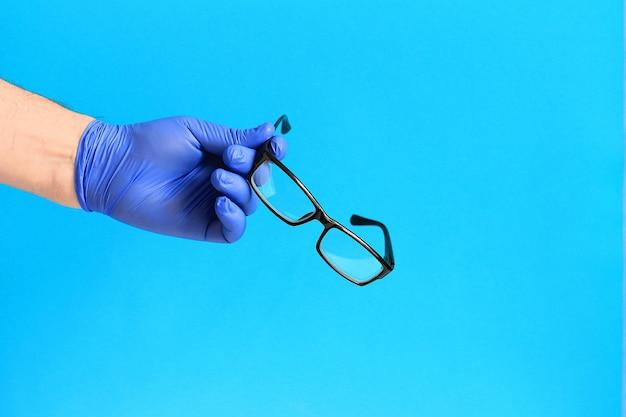 Gafas en la mano de un hombre, fondo azul, manos en guantes azules