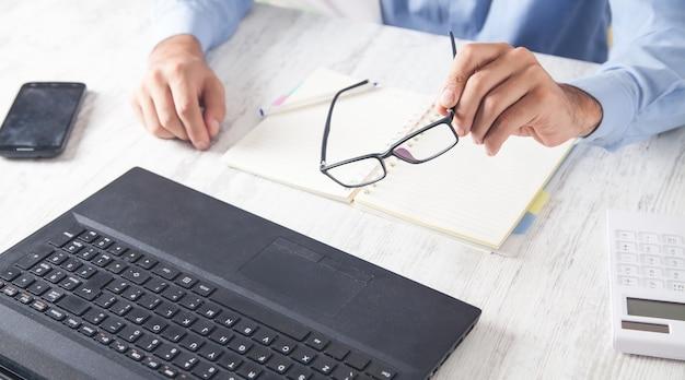Gafas de mano de hombre trabajando en oficina.