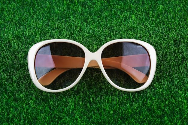 Gafas marrones se encuentran en la hierba verde. el concepto de verano, ocio, vacaciones, vacaciones.
