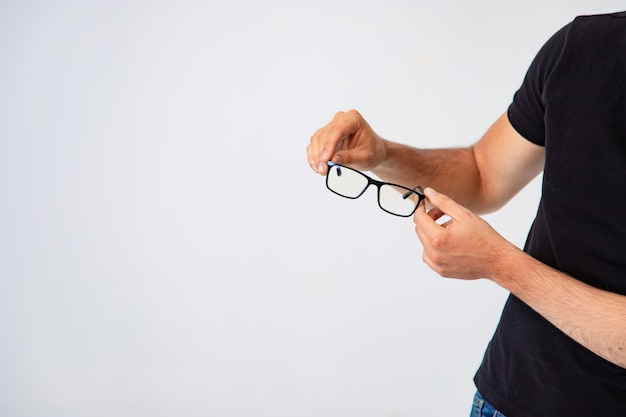 Las gafas de moda con montura negra están en manos de un hombre.