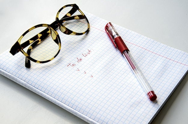 Gafas con montura de cuerno, bolígrafo de tinta roja en un cuaderno a cuadros. la hoja dice