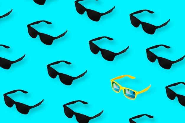 Gafas negras sobre fondo azul pastel