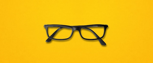Gafas de ojo negro aisladas en banner de fondo amarillo