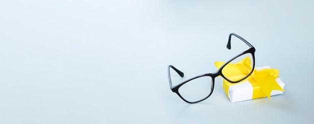 Gafas de ojo negro y pequeño regalo sobre fondo azul claro banner web