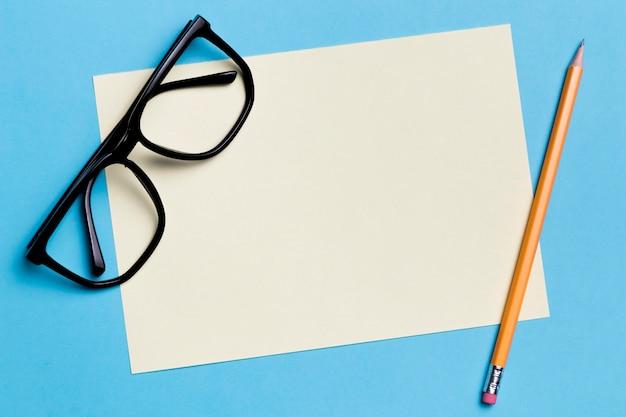 Gafas de primer plano con papel y lápiz