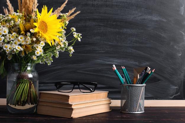 Gafas profesor libros y flores silvestres bouquet sobre la mesa, en la pizarra con tiza.