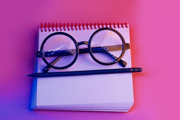 Gafas redondas negras se encuentran en un bloc de notas en luz de neón sobre fondo rosa