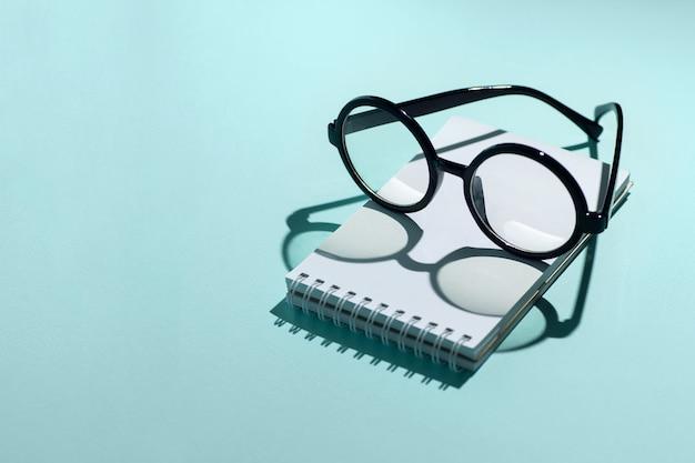 Gafas redondas negras se encuentran en un bloc de notas y proyectan sombras
