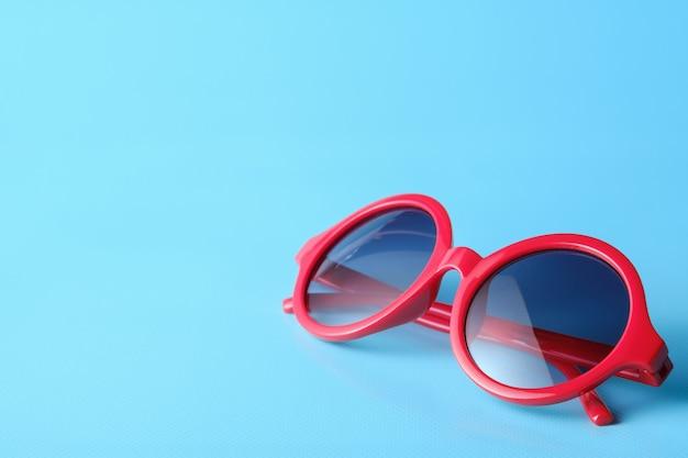 Gafas rojas sobre fondo azul con espacio de copia