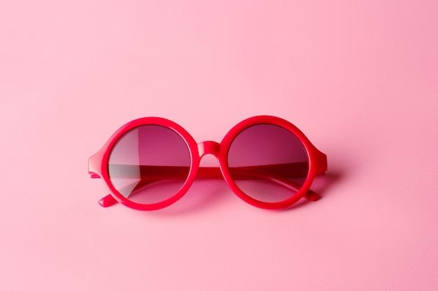 Gafas rojas sobre fondo rosa con espacio de copia