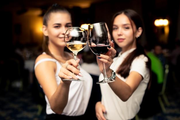 Gafas con rojo y blanco culpables en manos de hermosas chicas vestidas con blusas blancas