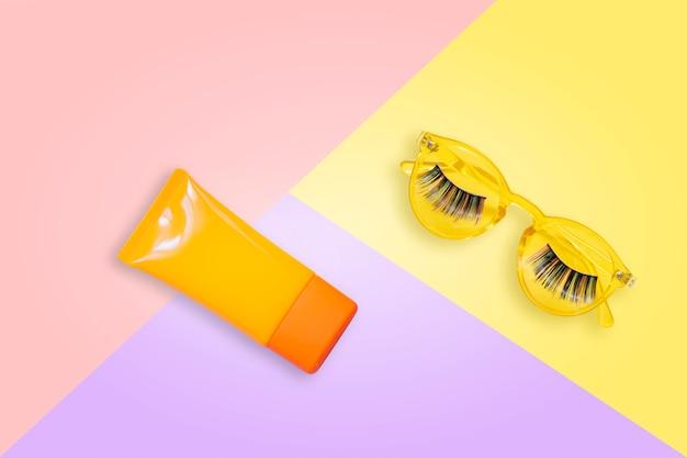 Gafas de sol amarillas con pestañas postizas y crema de protección solar naranja spf sobre fondo rosa.