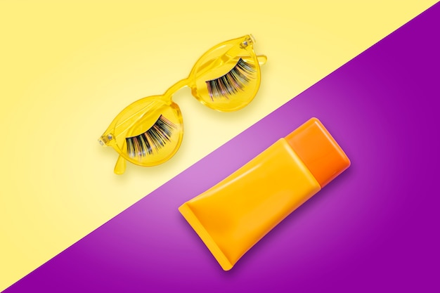 Gafas de sol amarillas con pestañas postizas y crema de protección solar naranja spf sobre fondo violeta.